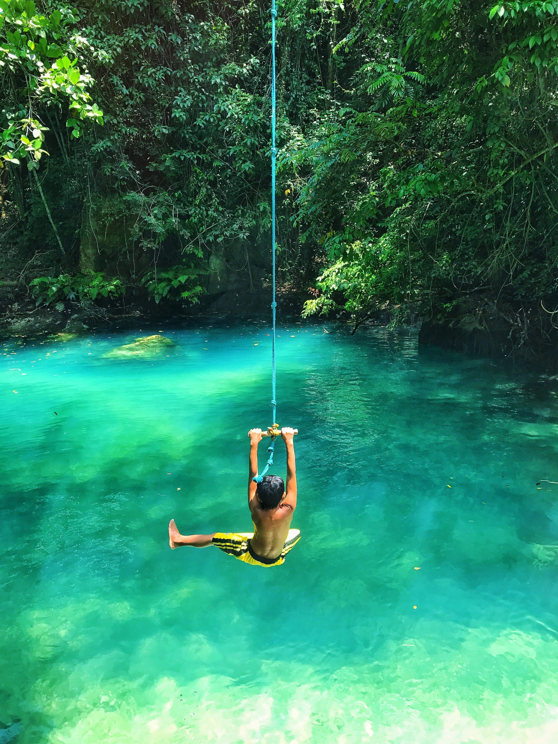 photo-of-boy-swinging-over-body-of-water-2413238-scaled